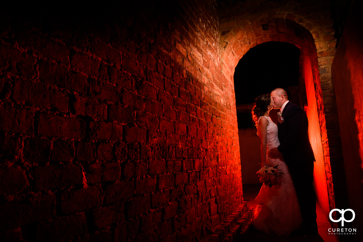 Creative wedding photo of a couple kissing at Old Cigar Warehouse under an archway at night.