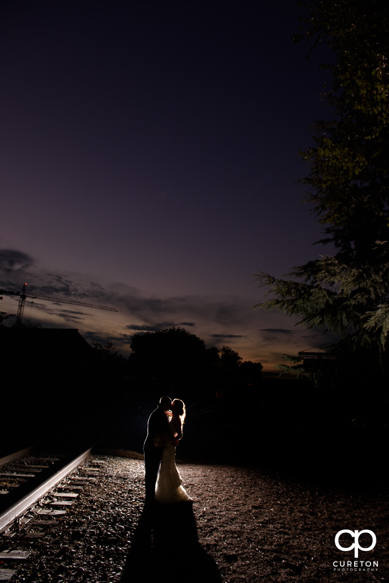 Backlit photo of a bride and groom at sunset.
