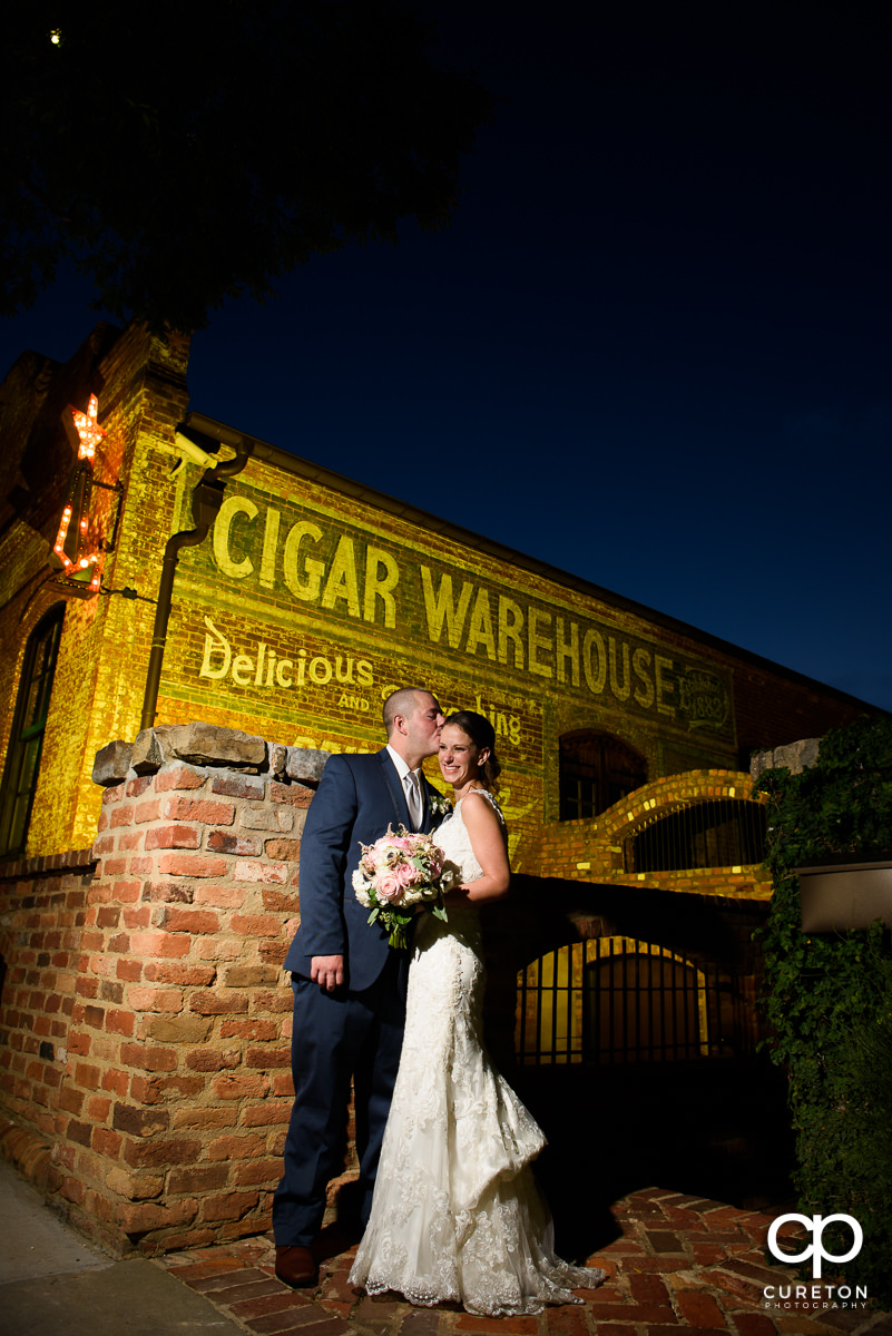 Groom kissing his bride on the cheek at their Old Cigar Warehouse wedding in Greenville,SC.
