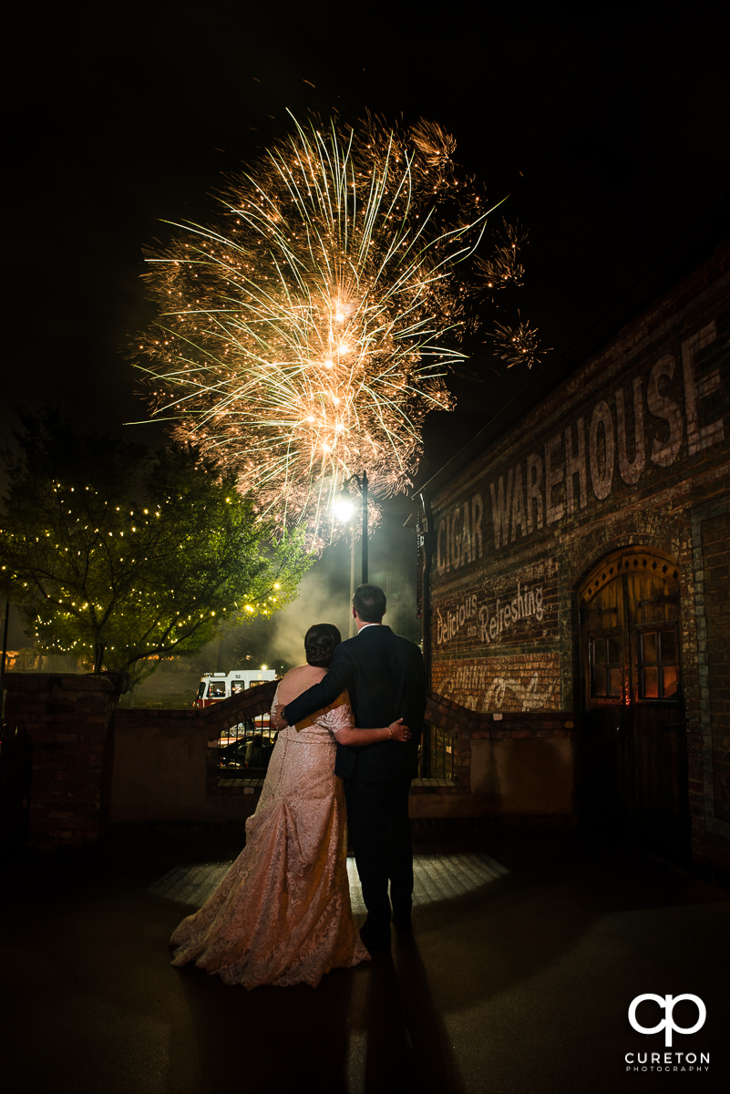 Bride and groom watching fireworks in downtown Greenville,SC after their wedding at The Old Cigar Warehouse in downtown Greenville,SC.