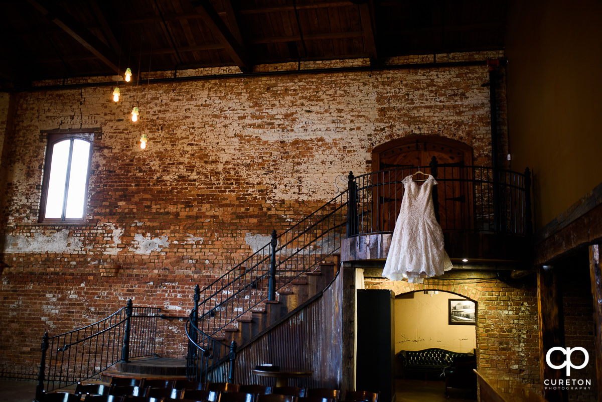 Wedding dress hanging on the staircase at Old Cigar Warehouse.