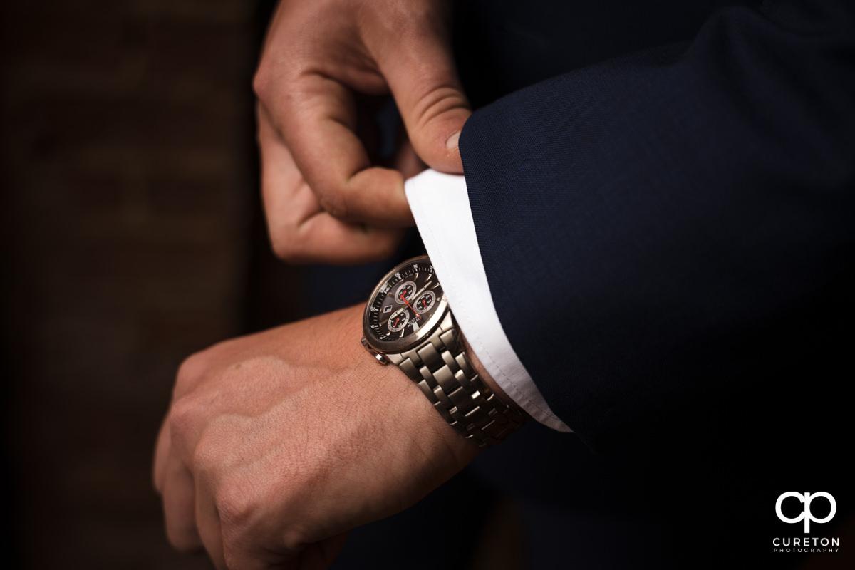 Groom adjusting his cuffs.