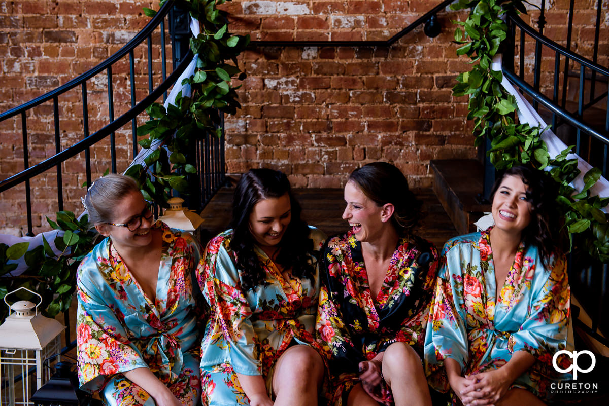 Bride and her bridesmaids laughing in their robes.