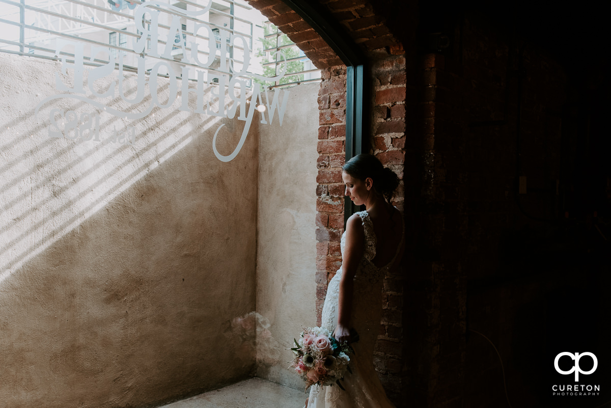 Bride looking out the huge window in the cellar at Old Cigar Warehouse before her wedding ceremony.