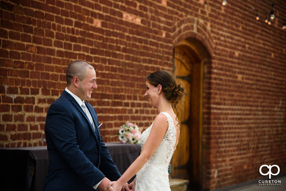 Bride and groom having a first look before their wedding ceremony at The Old Cigar Warehouse in Greenville,SC.