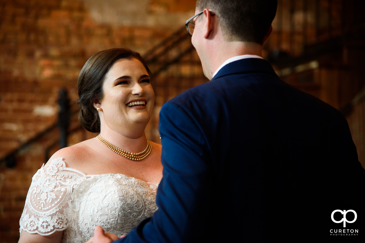 Bride smiling at her groom at a first look before the wedding ceremony.