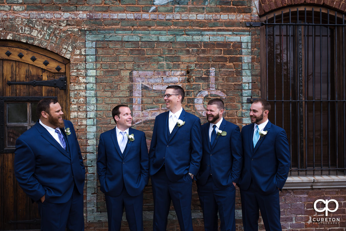 Groom laughing with his groomsmen on the deck of The Old Cigar Warehouse.