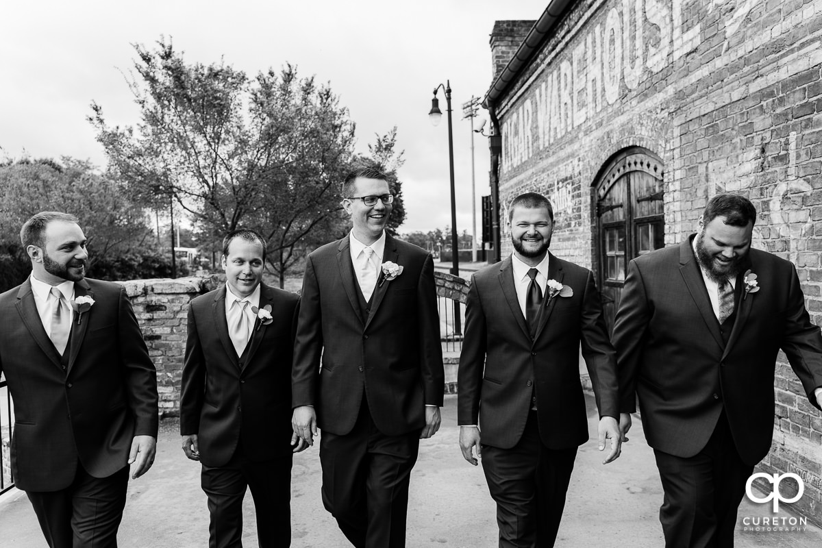 Groom walking with his groomsmen on the deck of The Old Cigar Warehouse.