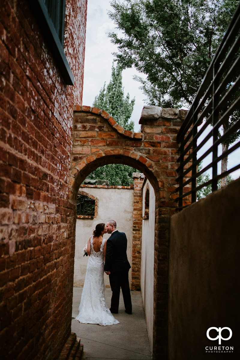 Bride and groom kissing though an archway at The Old Cigar Warehouse on their wedding day.