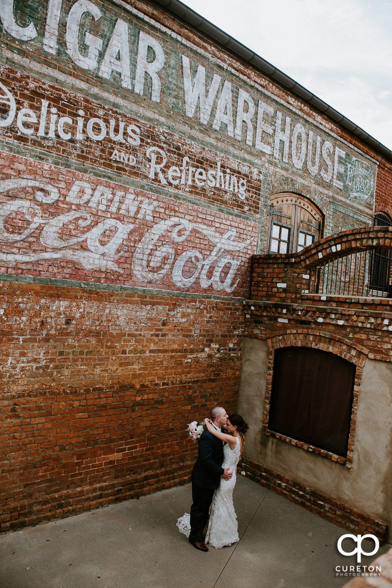 Bride and groom dancing below Main street level at The Old Cigar Warehouse.