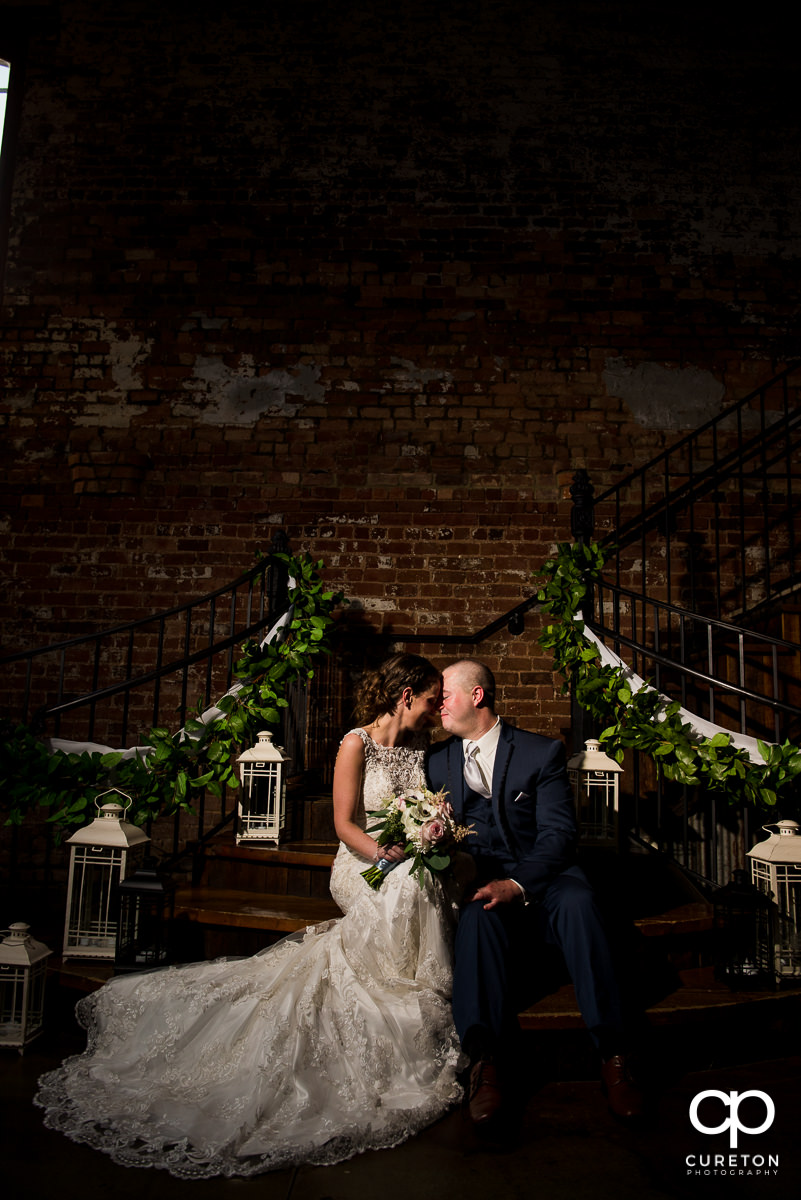 Bride and groom on the grand staircase in the Main Hall at The Old Cigar Warehouse in Greenville,SC.