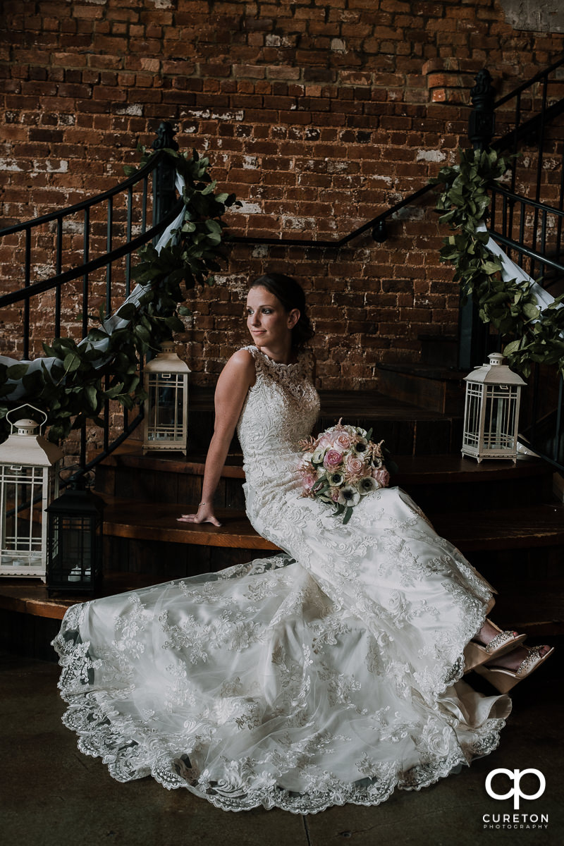 Bride sitting on the steps at the Old Cigar Warehouse.