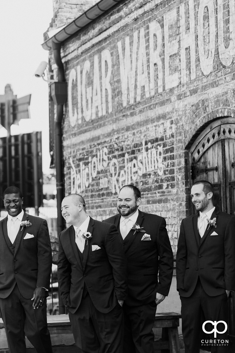 Black and white photo of groomsmen laughing.