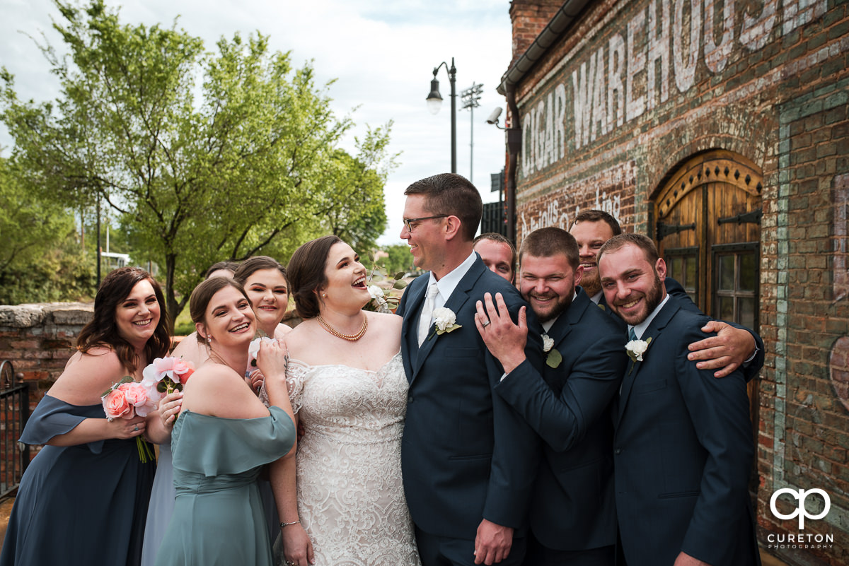 Bride and groom being hugged by the bridal party.