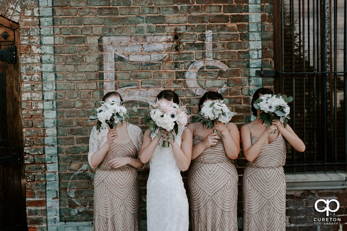 Bridesmaids holding flowers over their faces outside of Old Cigar Warehouse in Greenville.
