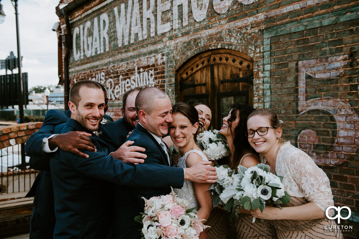 Wedding party hugging outside before the Old Cigar Warehouse wedding ceremony in Greenville,SC.