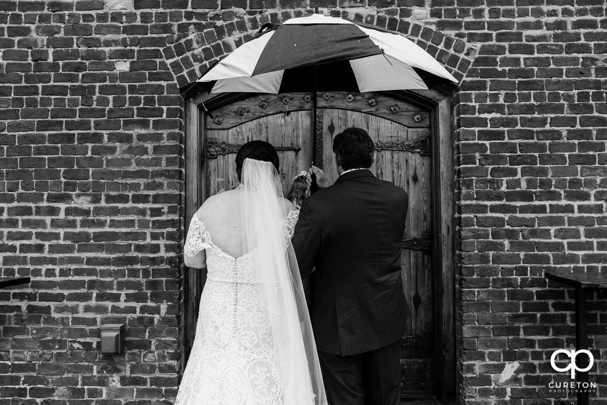 Bride and her father holding an umbrella in the rain preparing to walk down the aisle at her wedding.
