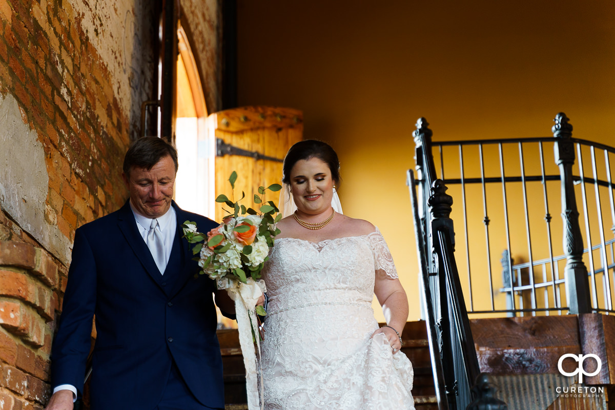 Bride and her dad walking down the staircase at Old Cigar Warehouse.