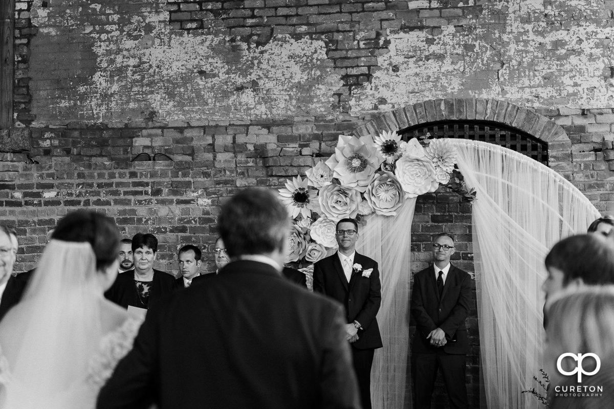 Groom watching his bride walking down the aisle.