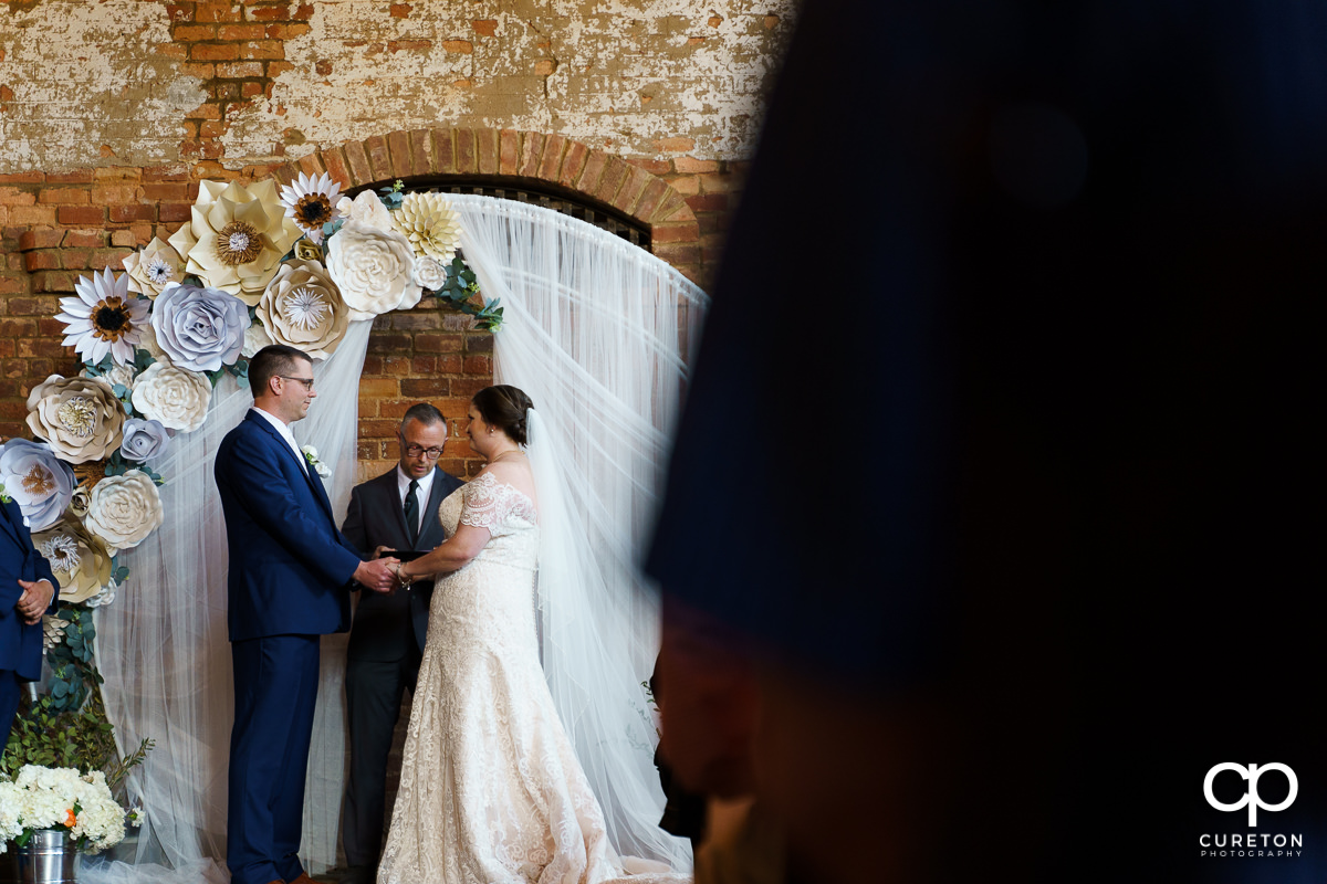 Groom holding his bride's hand during the wedding ceremony.