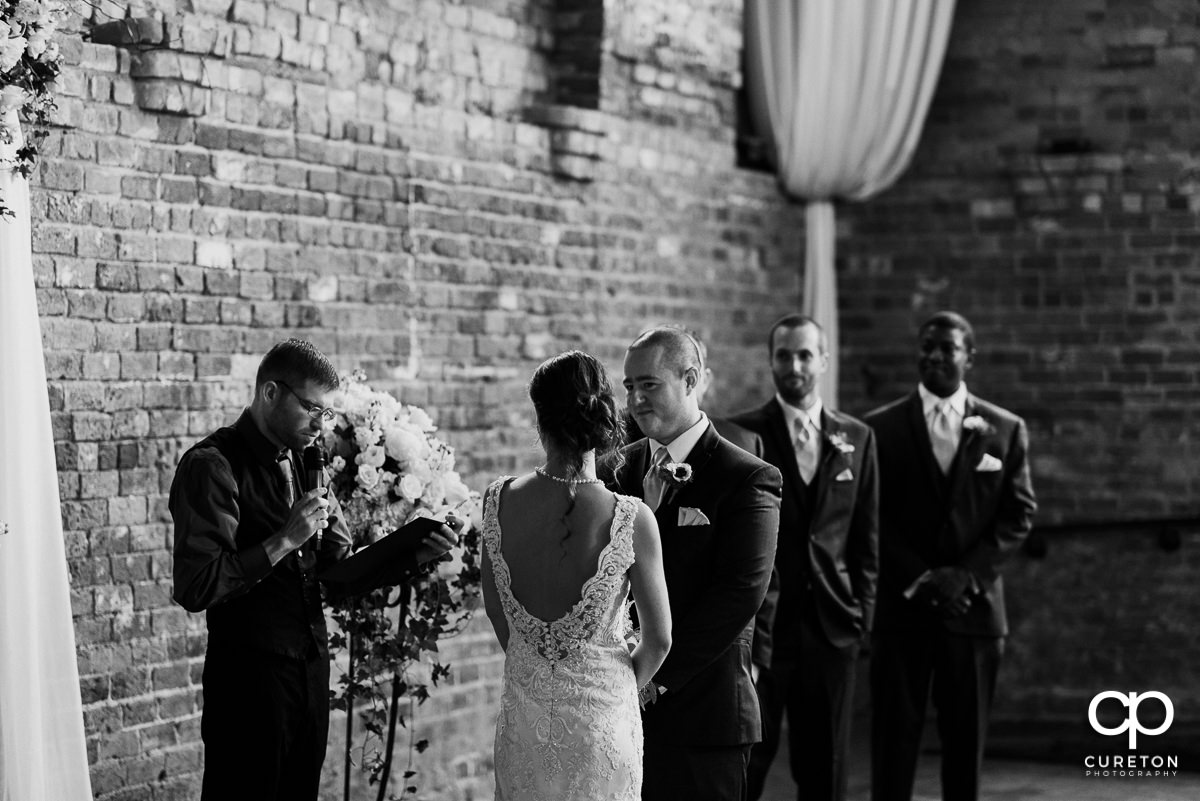 Groom looking at his bride as they say their vows.