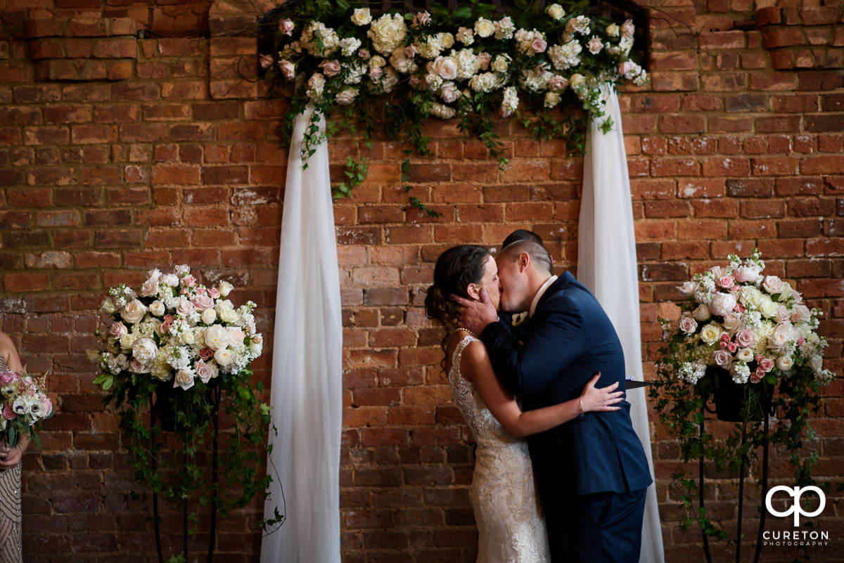 First kiss underneath a floral arch at The Old Cigar Warehouse.