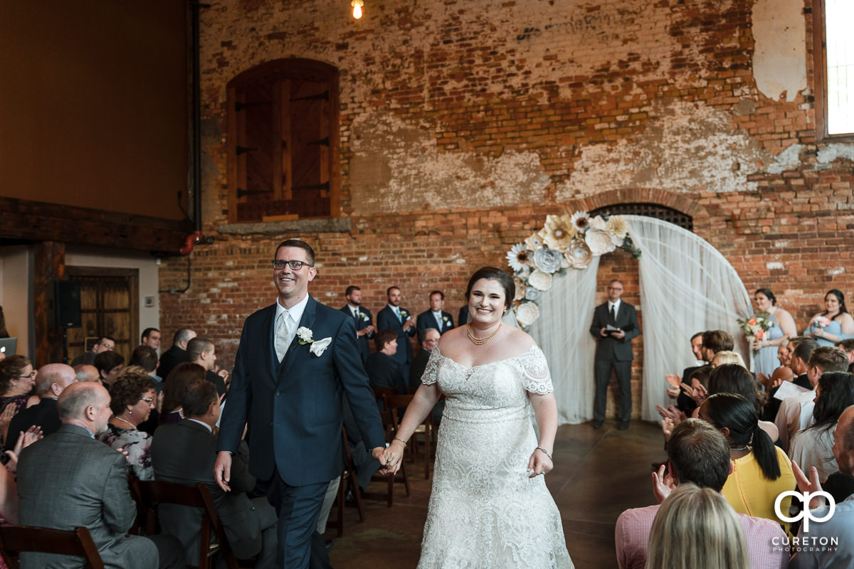 Bride and groom smiling walking back up the aisle after being pronounced husband and wife.