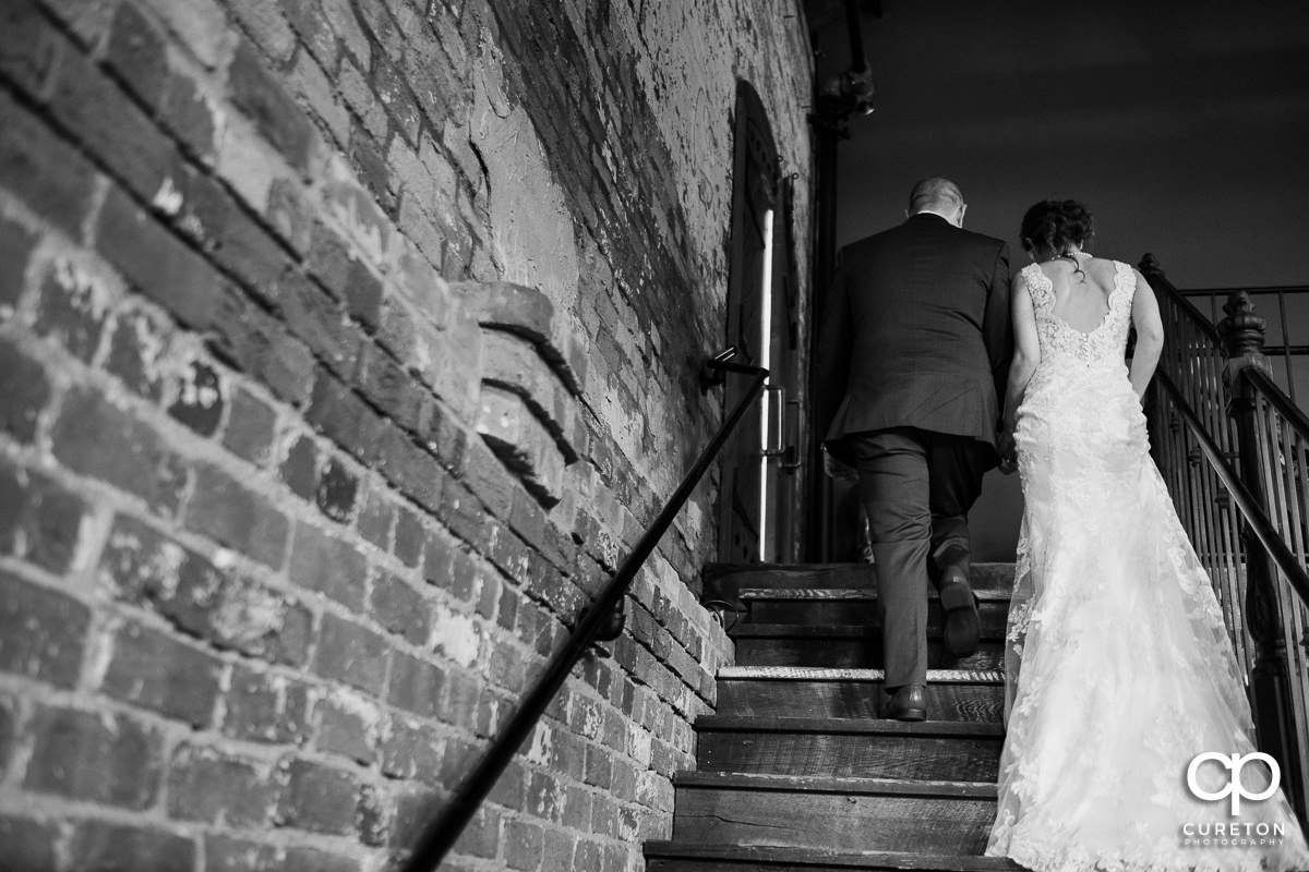 Bride and groom walking back up the staircase.