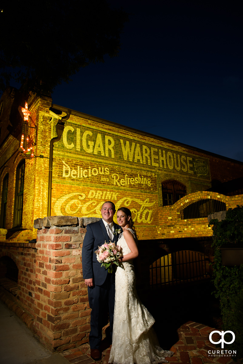 Bride and groom standing outside of the Old Cigar Warehouse at night.