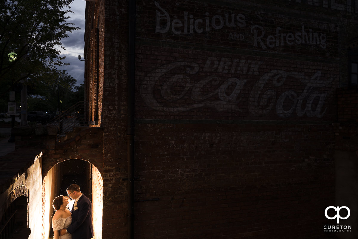 Bride and groom backlit in an archway at twilight in downtown Greenville,SC.