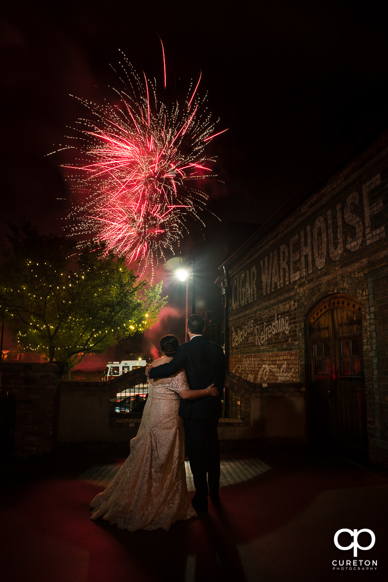Bride and groom watching the Greenville Drive's fireworks from the deck of the Old Cigar Warehouse