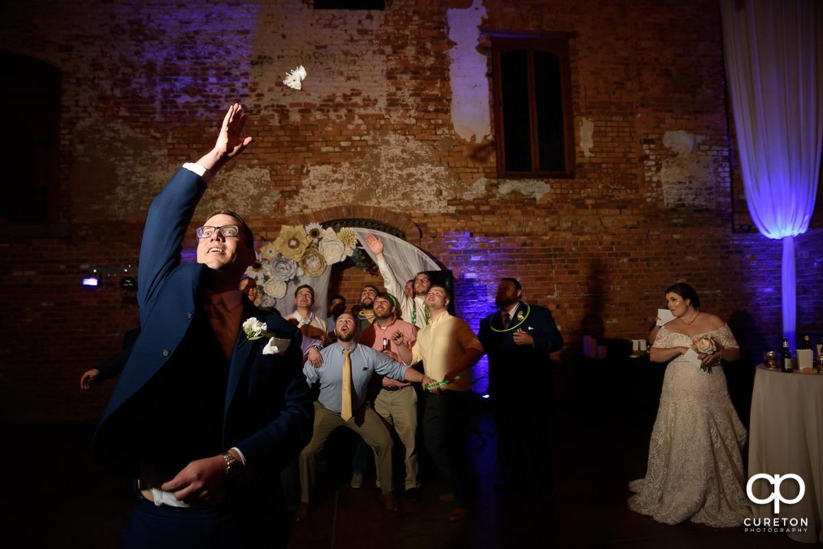 Groom tossing the bride's garter.