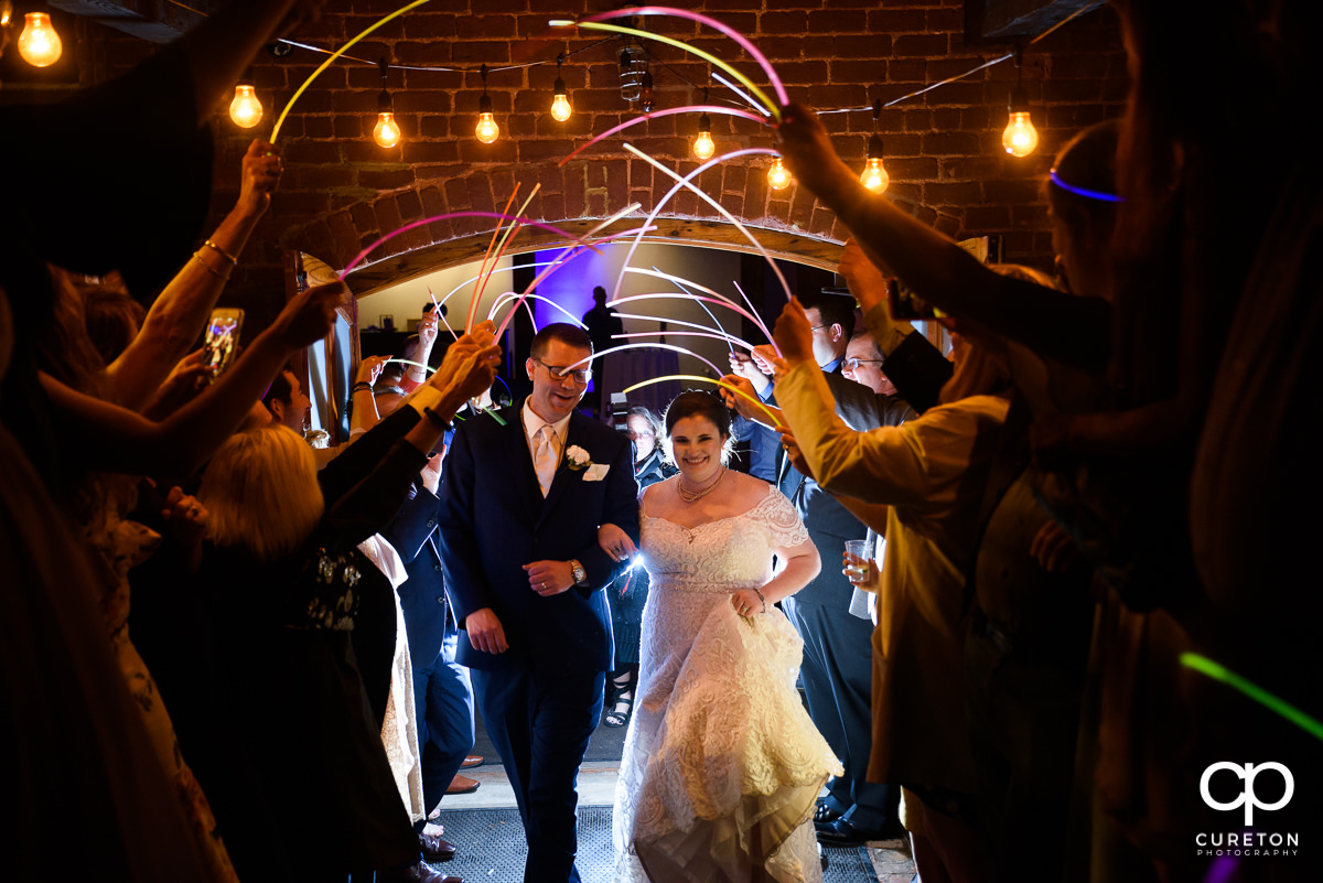 Bride and groom making a grand exit though glow sticks at The Old Cigar Warehouse wedding.