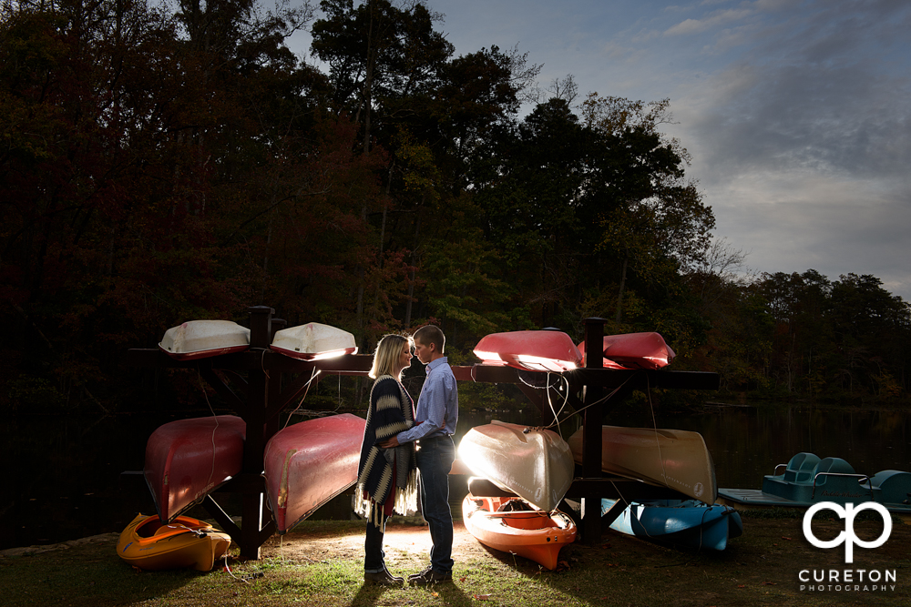 Couple standing by the boats near the lake during their Paris mountain engagement session in Greenville South Carolina.