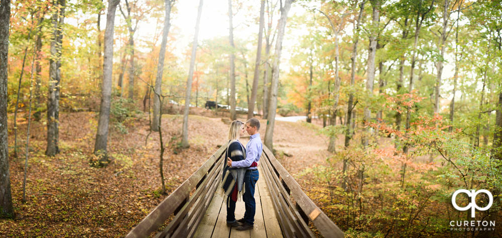 Future bride and groom standing on the bridge during their Paris mountain engagement session.