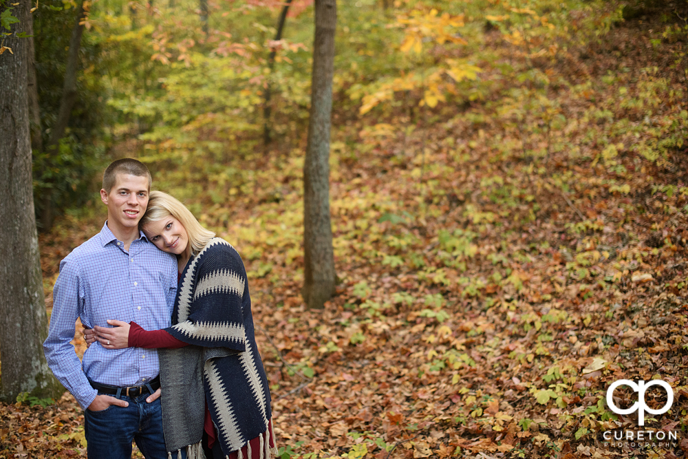 Briding groom hugging in the middle of the fall leaves .