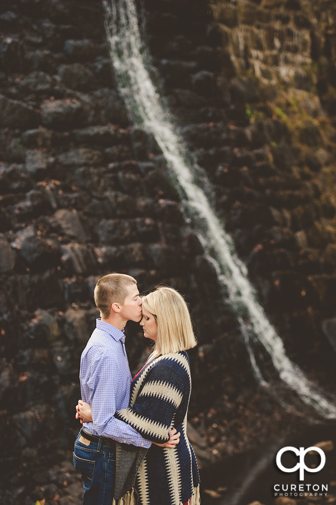 Man kissing his fiancée on the forehead in front of the dam at Paris Mountain State Park during their engagement session.