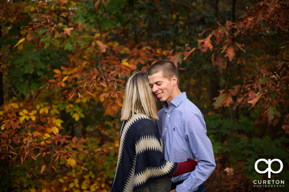 Woman making her fiancé laugh during their engagement session.