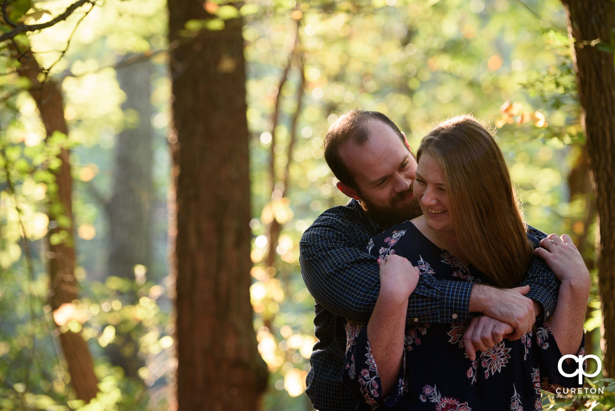 Future bride and groom laughing during their engagement session at Paris Mountain State Park in Greenville,SC.