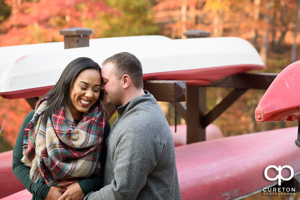 Future bride and groom cuddling during their Paris Mountain State Park Engagement Session in Greenville,SC.