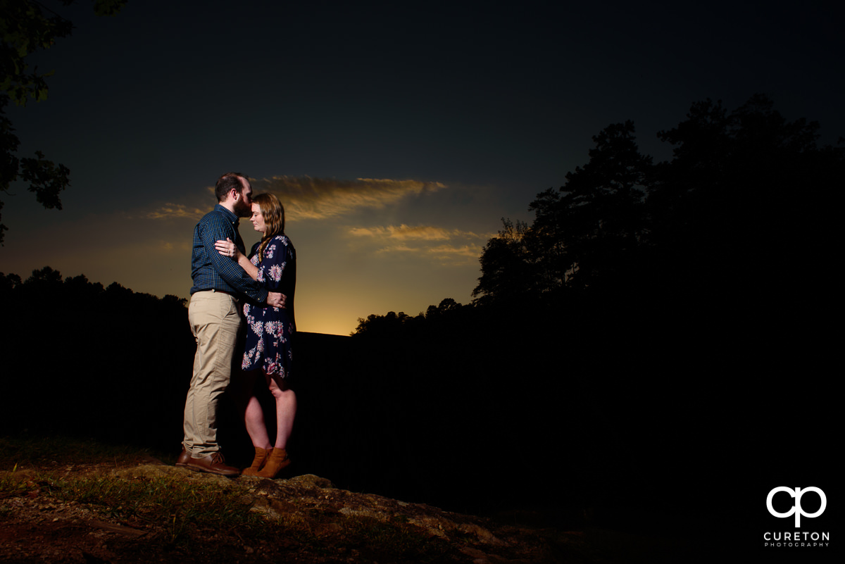 Groom kissing his future bride on the forehead at sunset during an engagement session at Paris Mountain State Park in Greenville,SC.