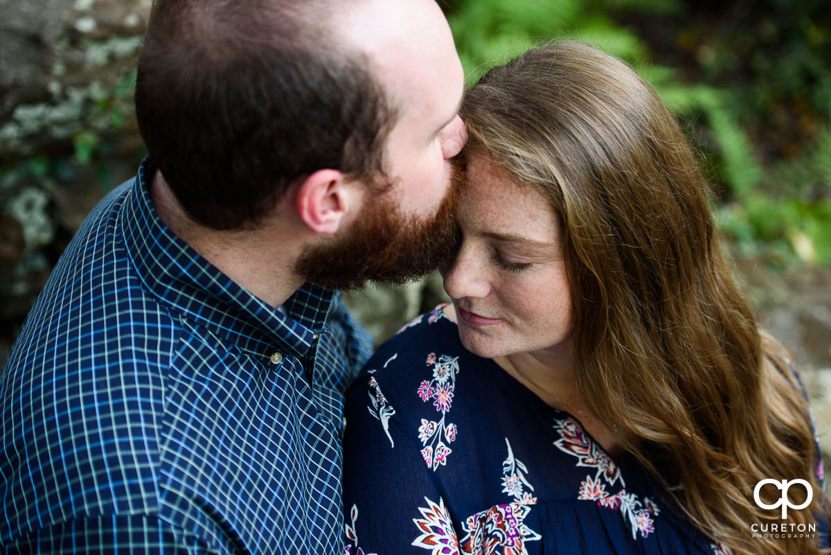 Man kissing his fiancee on the forehead.