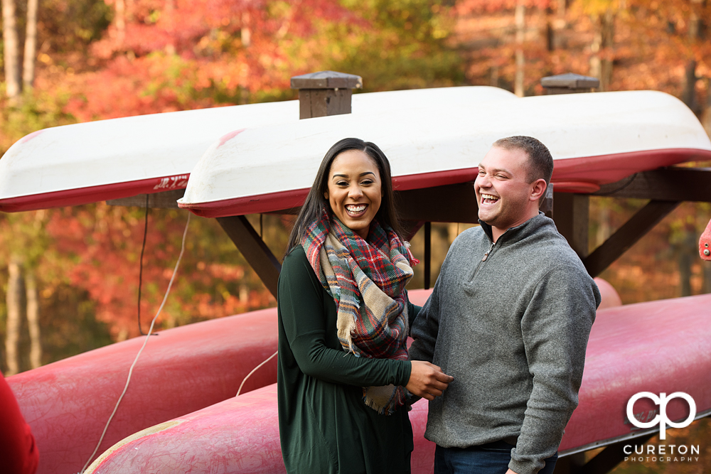 Engaged couple laughing by the boats on the pond during their Paris Mountain State Park Engagement Session in Greenville,SC.