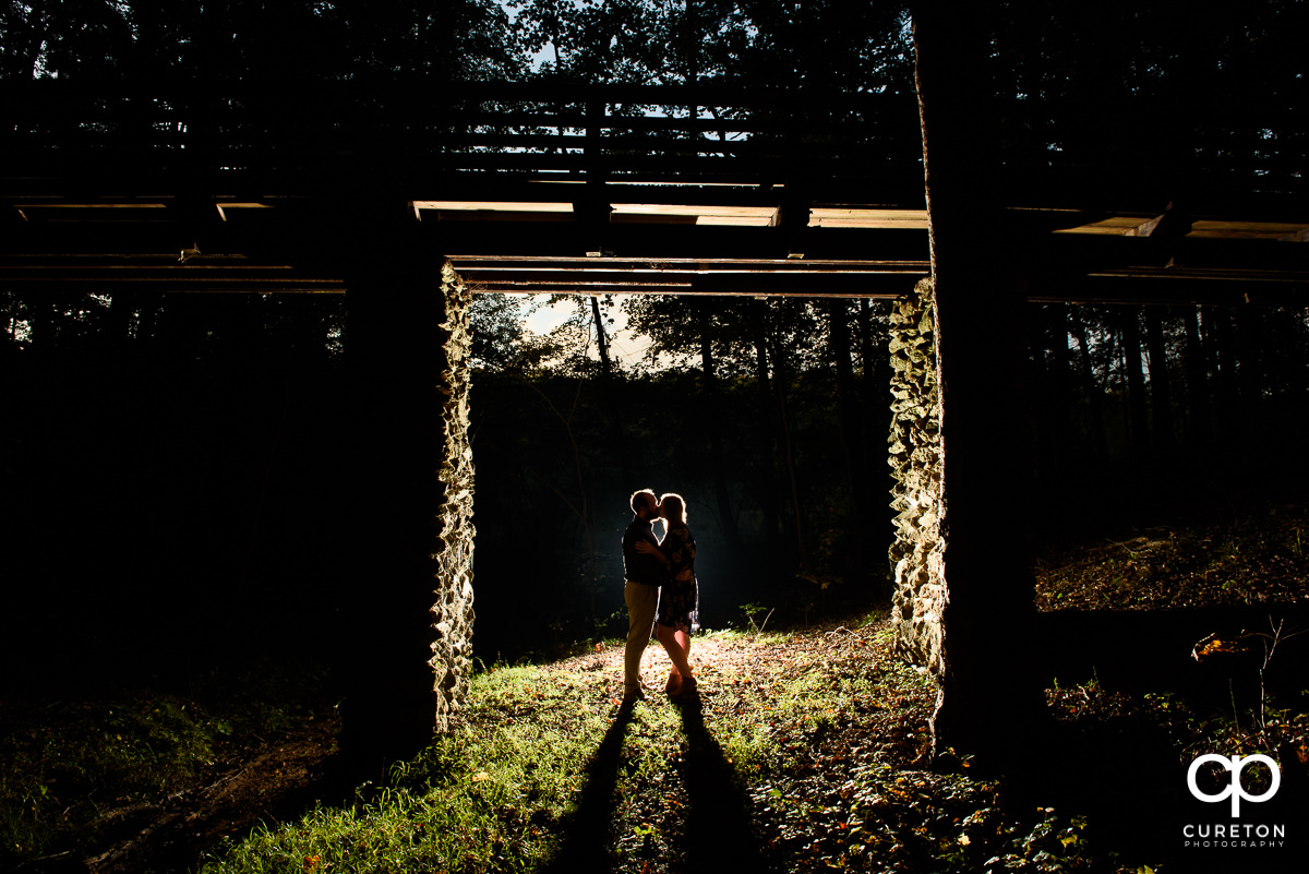 Backlit shot of a bride and groom underneath a walking bridge in the woods at an engagement session at Paris Mountain State Park in Greenville,SC.