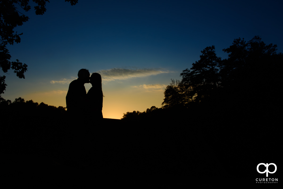 Sunset silhouette of an engaged couple at Paris Mountain State Park.