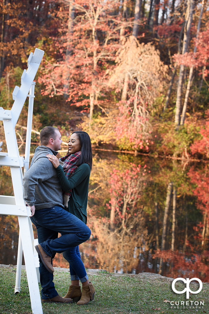 Engaged couple by the lake with fall leaves in the background.