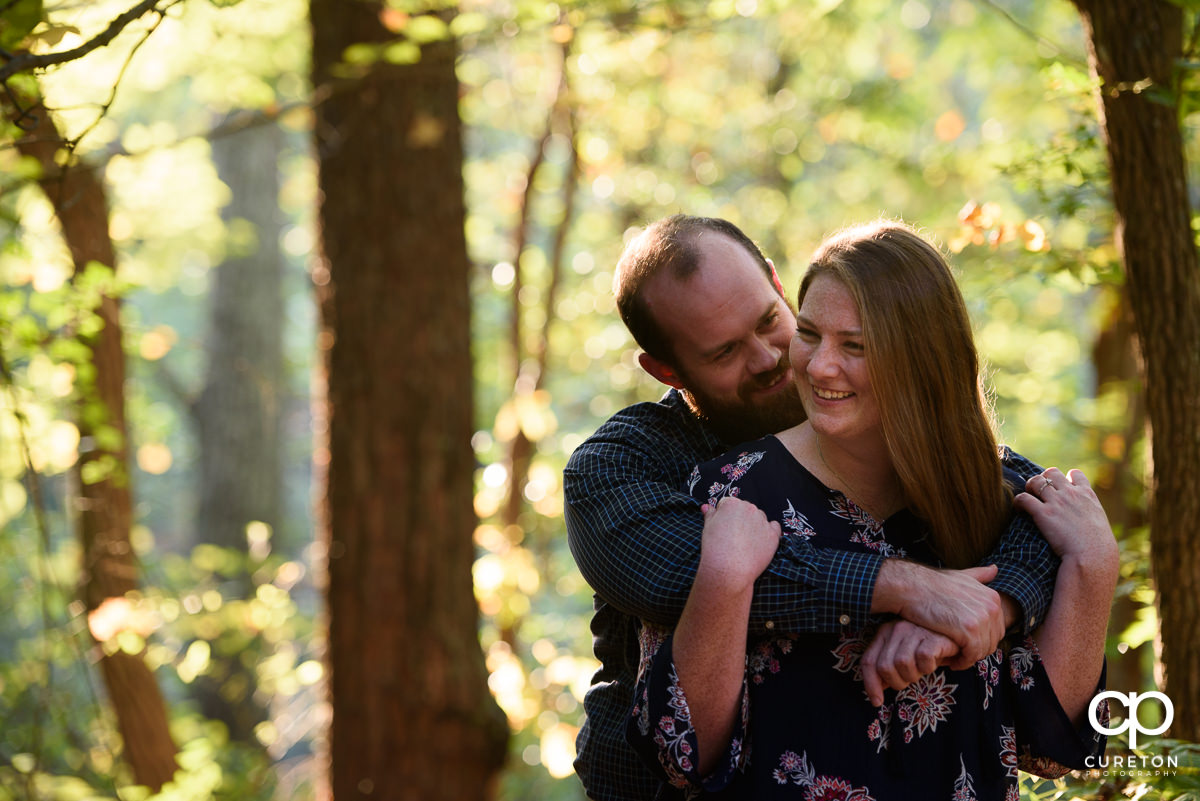 Bride and groom hugging in the woods during their engagement session.