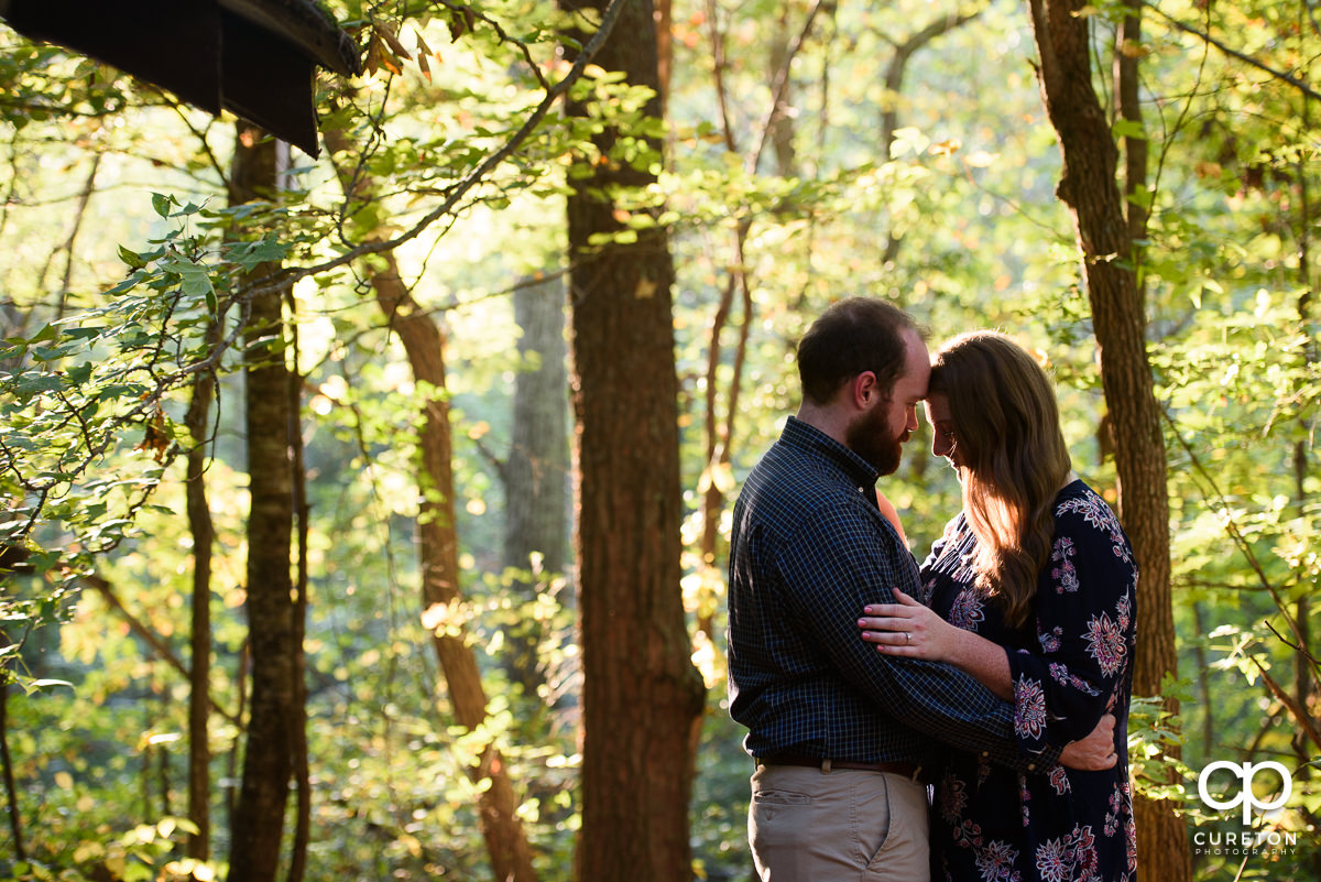 Engaged man and woman at Paris Mountain State Park during the fall.