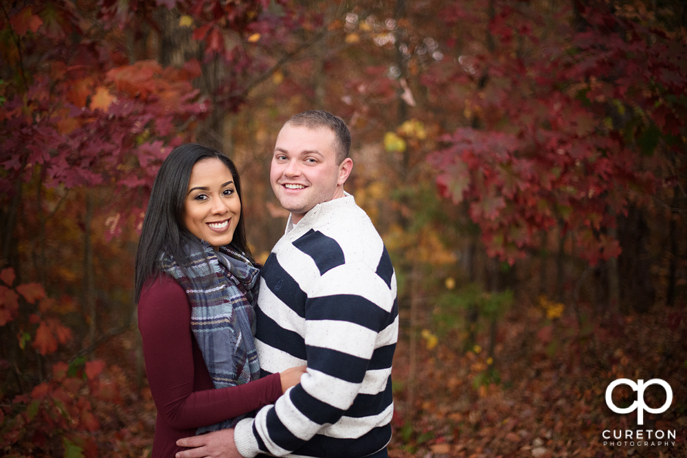 Engaged couple with a beautiful fall leaf background.