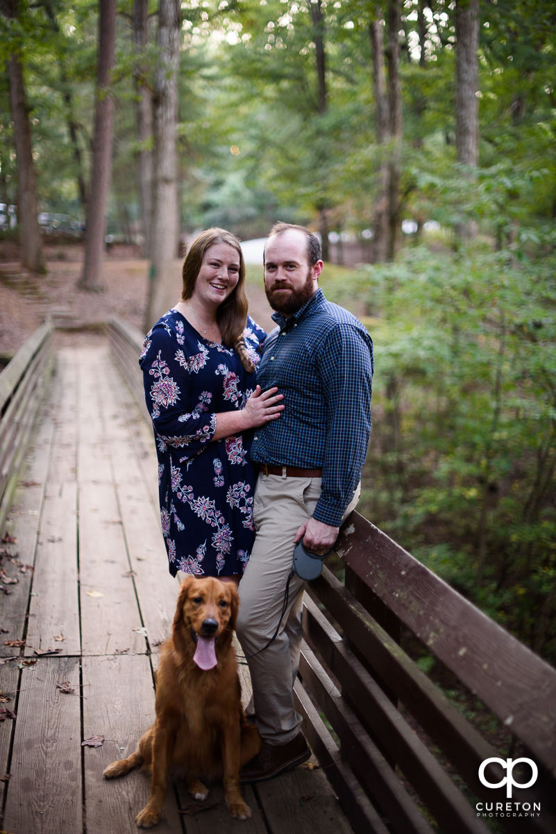 Future bride and groom on a bridge with their dog at Paris Mountain State Park.